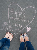 Día de madres - dibujo de tiza de la forma del corazón y los pies de un niño Fotos de archivo libres de regalías