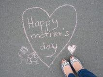 Día de madres - dibujo de tiza de la forma del corazón y los pies de una madre Foto de archivo libre de regalías