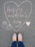 Día de madres - dibujo de tiza de la forma del corazón y los pies de una madre Imagen de archivo