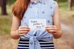 Día de madres feliz - muchacha con el texto en tarjeta en la naturaleza fotos de archivo libres de regalías