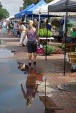 Día de mercado con los compradores con la reflexión del comprador de la mujer Foto de archivo libre de regalías