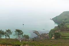 Día de niebla en la costa con la hierba verde en las rocas Crozon, Francia 29 de mayo de 2018 Fotografía de archivo