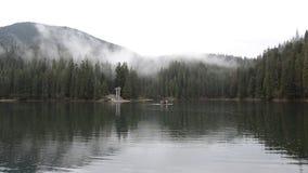 Día de niebla lluvioso en el lago Synevyr de la montaña en qué flotadores una balsa con los turistas almacen de metraje de vídeo