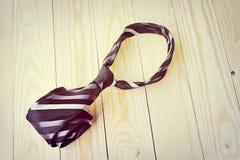 Día de padres feliz con la corbata rayada roja, gris y negra en fondo de madera de pino en estilo del vintage Imagenes de archivo