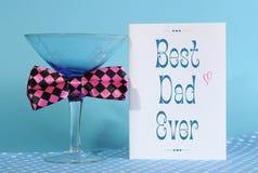 Día de padres feliz, el mejor papá nunca, tarjeta de felicitación con el vidrio azul de martini Foto de archivo libre de regalías