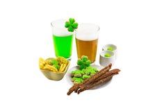 Día de Patrick's del santo un par de vidrios de verde de la cerveza festivos y de trigo para el trébol de la galleta del bocado Fotos de archivo libres de regalías