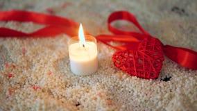 Día de San Valentín de la decoración con la quema de la vela y cinta en la arena