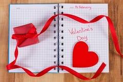 Día de tarjetas del día de San Valentín escrito en el cuaderno, el regalo envuelto y el corazón, decoración para las tarjetas del Fotos de archivo libres de regalías
