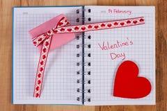 Día de tarjetas del día de San Valentín escrito en el cuaderno, el regalo envuelto y el corazón, decoración para las tarjetas del Imagen de archivo