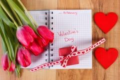 Día de tarjetas del día de San Valentín escrito en el cuaderno, los tulipanes frescos, el regalo envuelto y el corazón, decoració Foto de archivo libre de regalías