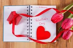 Día de tarjetas del día de San Valentín escrito en el cuaderno, los tulipanes frescos, el regalo envuelto y el corazón, decoració Imagen de archivo