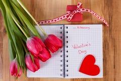 Día de tarjetas del día de San Valentín escrito en el cuaderno, los tulipanes frescos, el regalo envuelto y el corazón, decoració Foto de archivo
