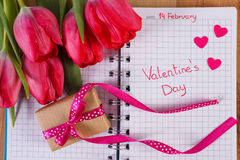Día de tarjetas del día de San Valentín escrito en el cuaderno, los tulipanes frescos, el regalo envuelto y los corazones, decora Fotos de archivo libres de regalías