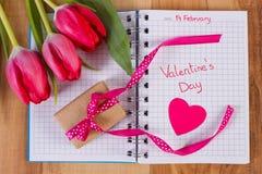 Día de tarjetas del día de San Valentín escrito en el cuaderno, los tulipanes frescos, el regalo envuelto y los corazones, decora Fotografía de archivo