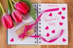 Día de tarjetas del día de San Valentín escrito en el cuaderno, los tulipanes frescos, el regalo envuelto y los corazones, decora Imagen de archivo