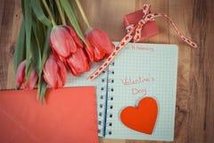 Día de tarjetas del día de San Valentín escrito en el cuaderno, los tulipanes frescos, la letra de amor, el regalo y el corazón,  Fotografía de archivo