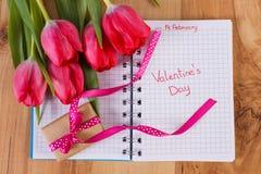 Día de tarjetas del día de San Valentín escrito en el cuaderno, los tulipanes frescos y el regalo envuelto, decoración para las t Imagen de archivo libre de regalías