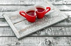 Día de tarjetas del día de San Valentín rojo de la bebida del té de las tazas en forma de corazón Fotografía de archivo
