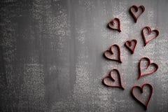Día de tarjetas del día de San Valentín y concepto del amor Muchos corazones rojos de papel en fondo de madera gris imagenes de archivo