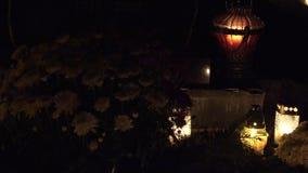 Día de todo absolutamente Las velas queman en sepulcros en el cementerio en la noche Cambio del foco 4K almacen de metraje de vídeo