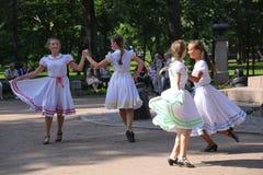 Día de verano soleado en el parque de la ciudad actores públicos de las muchachas que bailan con la gente de los turistas bajo mú Imagenes de archivo