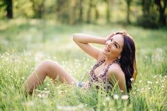 Día de verano soleado, mujer joven hermosa que miente en la hierba Fotos de archivo