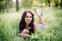 Día de verano soleado, mujer joven hermosa que miente en la hierba Imagen de archivo libre de regalías