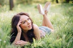Día de verano soleado, mujer joven hermosa que miente en la hierba Foto de archivo libre de regalías