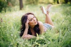 Día de verano soleado, mujer joven hermosa que miente en la hierba Foto de archivo