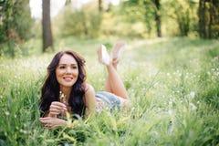 Día de verano soleado, mujer joven hermosa que miente en la hierba Fotografía de archivo