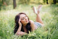 Día de verano soleado, mujer joven hermosa que miente en la hierba Imagen de archivo