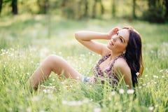 Día de verano soleado, mujer joven hermosa que miente en la hierba Fotos de archivo libres de regalías