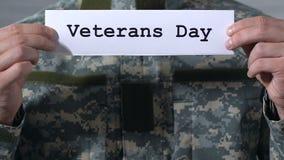 Día de veteranos escrito en el papel en las manos del soldado de sexo masculino, memoria de héroes almacen de video