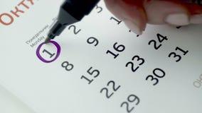 Día del círculo de la mano de la mujer en calendario del papel 1r día del mes almacen de metraje de vídeo