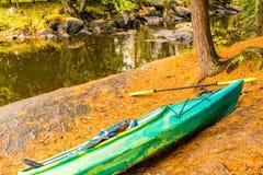 Día del otoño, kajak en el listo con un chaleco salvavidas y paleta cerca de la orilla fotos de archivo