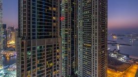 Día del puerto deportivo de Dubai al timelapse de la noche, a las luces que brillan y a los rascacielos más altos almacen de metraje de vídeo