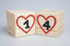 Día del `s de la tarjeta del día de San Valentín Cubos de madera con los un y cuatro corazones manuscritos del rojo del interior Imágenes de archivo libres de regalías