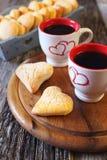 Día del ` s de la tarjeta del día de San Valentín: dos tazas de galletas del café y del corazón Fotografía de archivo