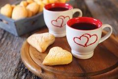 Día del ` s de la tarjeta del día de San Valentín: dos tazas de galletas del café y del corazón Imagen de archivo