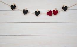 Día del `s de la tarjeta del día de San Valentín Hangin rojo y negro de los corazones en el cordón natural Fondo blanco de madera Foto de archivo libre de regalías