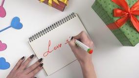 Día del ` s de la tarjeta del día de San Valentín, ejemplo, mujer que mano del ` s escribe en un cuaderno, amor apesta 60 fps