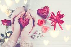 Día del `s de la tarjeta del día de San Valentín El par joven da sostener la caja de regalo sobre el fondo de madera blanco fotografía de archivo libre de regalías