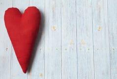 Día del `s de la tarjeta del día de San Valentín Fondo azul claro de madera Corazón hecho a mano de la materia textil Corazón roj foto de archivo