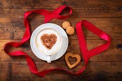Día del `s de la tarjeta del día de San Valentín Taza de café del capuchino con el corazón en espuma fotografía de archivo libre de regalías