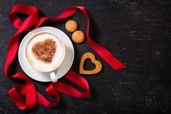 Día del `s de la tarjeta del día de San Valentín Taza de café del capuchino con el corazón en espuma imagen de archivo