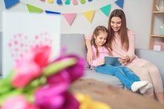 Día del ` s de las mujeres de la madre y de la hija junto en casa que juega la tableta digital fotos de archivo
