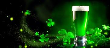 Día del ` s de St Patrick La pinta verde de la cerveza sobre el fondo verde oscuro, adornado con el trébol se va imagen de archivo libre de regalías