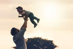 Día del `s del padre El padre alegre feliz que se divierte lanza para arriba en el ai Foto de archivo