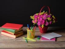 Día del ` s del profesor del mundo Todavía vida con la pila, las flores, el documento y el escritorio del libro sobre fondo negro Imagen de archivo