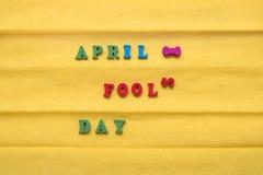 Día del día del tonto, inscripción de letras multicoloras en un fondo de papel amarillo Imagenes de archivo